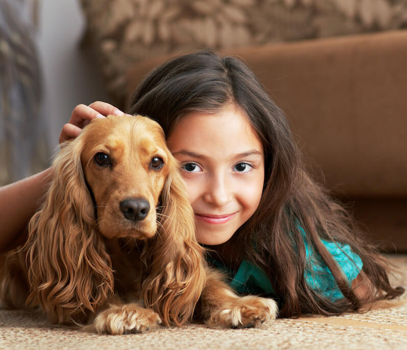 girl and dog laying on clean carpet in odgen home