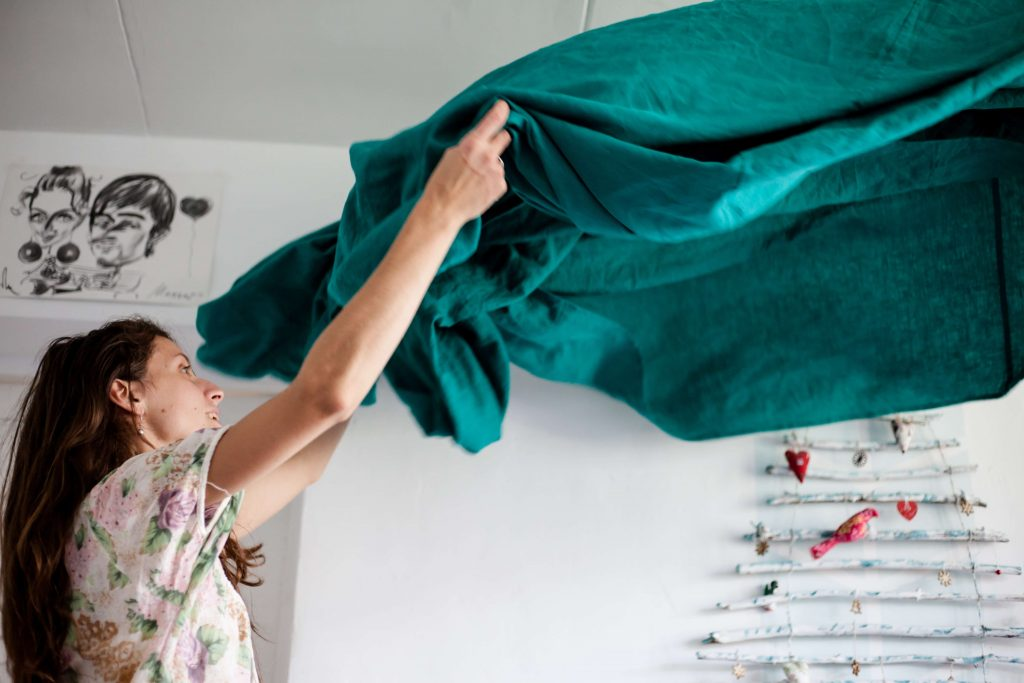 woman lifting up bedsheets