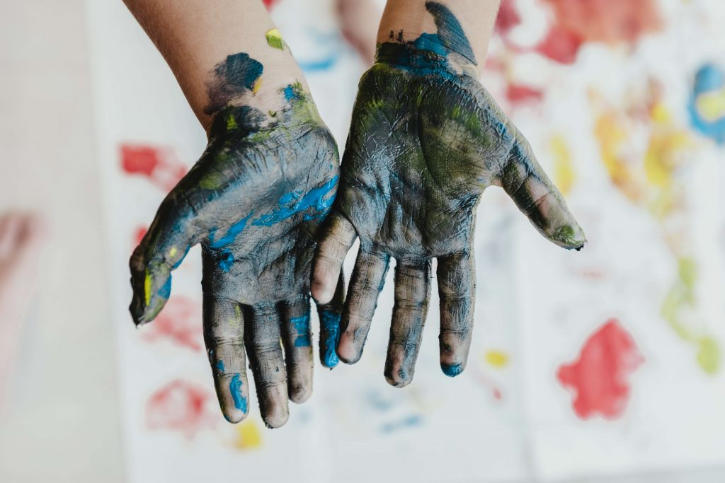 hands covered in messy paint